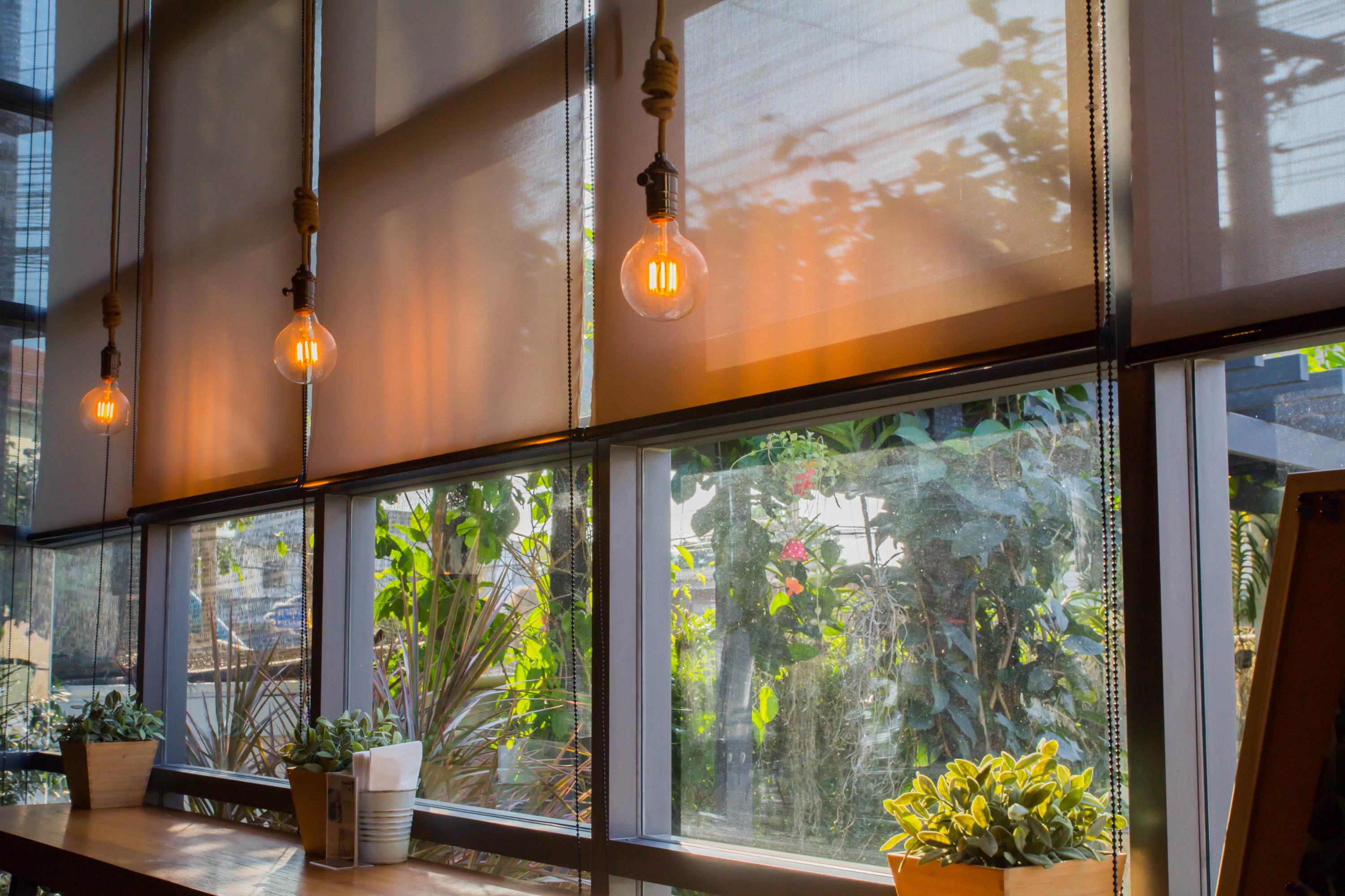four windows with orange toned blinds with foliage outside. three industrial light bulbs, K & M Carpets & Interiors, Shaftesbury Mews, Bath, Whiteway, Twerton, Bear Flat, The Oval, Southdown