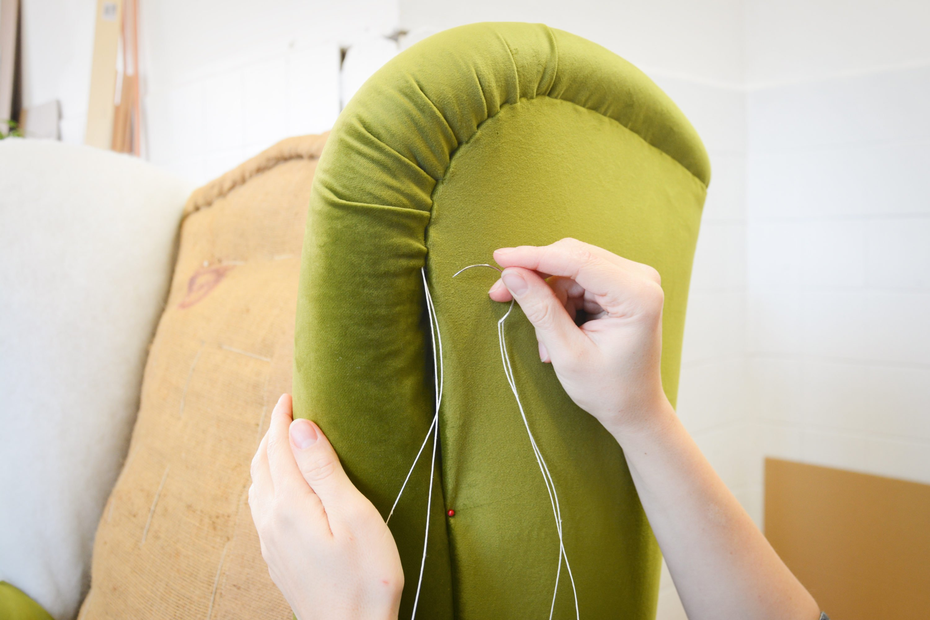 Person upholstering Green winged-back chair