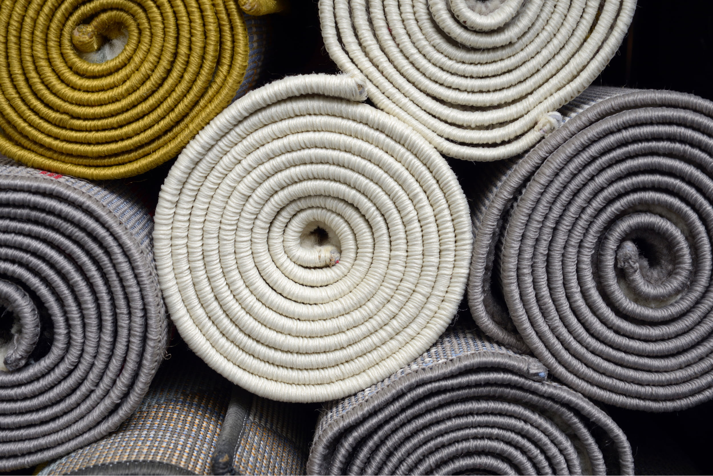 Seven rolled up rugs stacked on each other, K & M Carpets & Interiors, Shaftesbury Mews, Bath, Whiteway, Twerton, Bear Flat, The Oval, Southdown